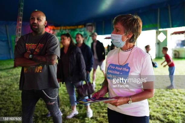 Volunteer passes out vaccination information to people waiting to enter the circus at a new 'Pop Up' vaccination centre in the Big Top of Circus...