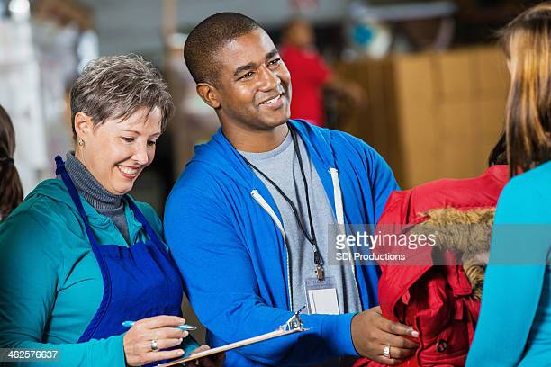 Volunteer passing out coats at charity clothing bank