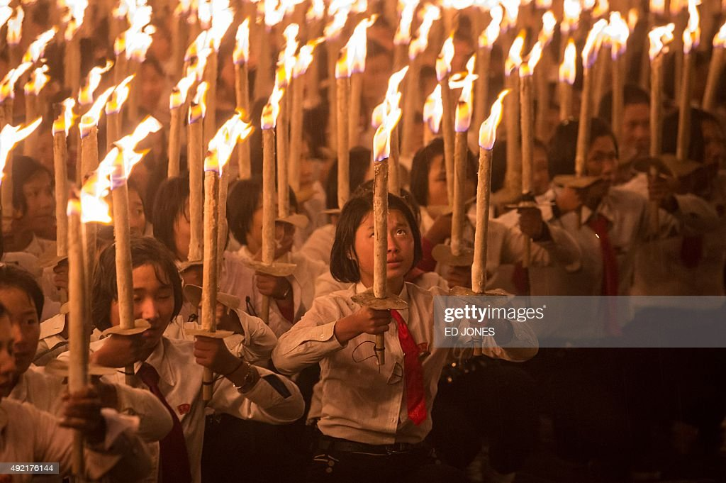 Volunteer performers hold burning torches during a torch-light performance at Kim Il-Sung square in Pyongyang on October 10, 2015. North Korea was marking the 70th anniversary of its ruling Workers' Party. AFP PHOTO / Ed Jones