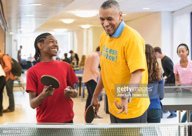Volunteer playing table tennis with boy in community center