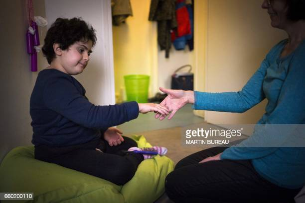 A volunteer plays with Lena a 8yearold autistic child on March 24 2017 in Courbevoie northwest of Paris at the Lud'Eveil center for children with...