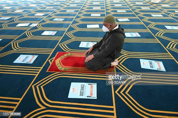 TOPSHOT A volunteer prays alone in the prayer hall which has signs on the carpet enforcing social distancing before the main Friday prayers at Madina...