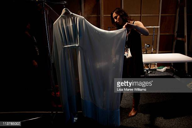 A volunteer prepares designs backstage ahead of the Ms Couture show during Rosemount Australian Fashion Week Spring/Summer 2011/12 at Overseas...