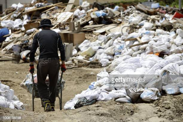 A volunteer pushes a loaded wheelbarrow during cleanup work on July 31 in Kure a Hiroshima Prefecture city heavily damaged by floods following...