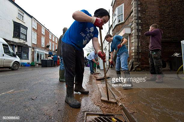 A volunteer pushes the remaining water down the drains on Tadcaster High Street on December 28 2015 in Tadcaster England Heavy rain over the...