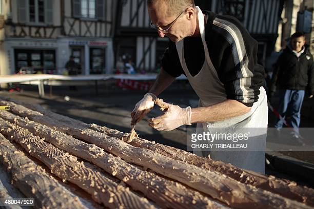 A volunteer puts cream on a traditional Christmas yule log cake during an attempt to set a new Guinness World Record with a 15 kilometre yule log...