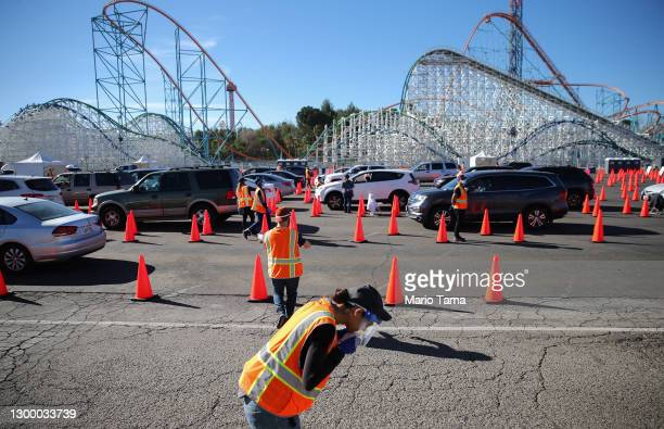 Volunteer puts on her face mask as other volunteers help guide motorists at a mass drive-thru COVID-19 vaccination site at a Six Flags Magic Mountain...