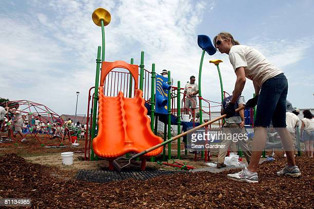 A volunteer rakes mulch by a newly installed slide at Fannie C Williams Elementary School during a playground rebuild sponsored by Nickelodeon on May...