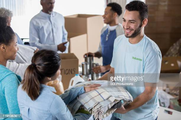 volunteer receives blankets during clothing drive - food drive stock pictures, royalty-free photos & images