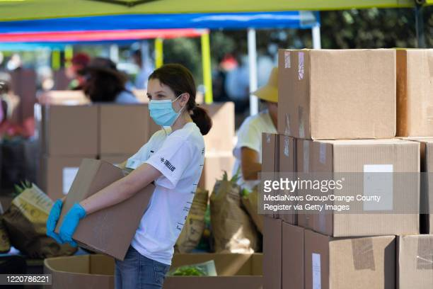 Volunteer Reece Baker waits for the next car during a drive-thru emergency food distribution in the parking lot of IKEA in Costa Mesa, CA on...