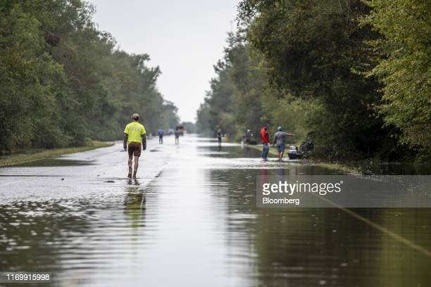 Volunteer rescue workers walk through a flooded highway following Tropical Storm Imelda in Fannett Texas US on Friday Sept 20 2019 The remnants of...