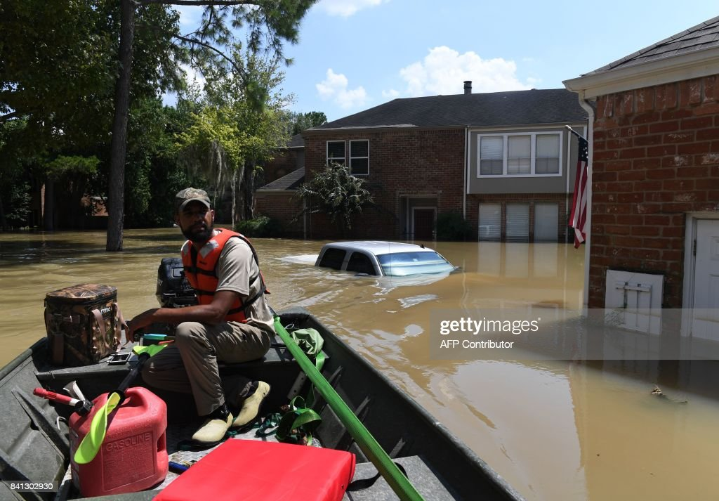 TOPSHOT - Volunteer rescuer Matt Clarke searches for local residents after a mandatory evacuation was ordered in the area beneath the Barker Reservoir as water is released, after Hurricane Harvey caused widespread flooding in Houston, Texas on August 31, 2017. Hurricane Harvey hit the Texas coast with over 3 feet of rain and 125 mph winds. /