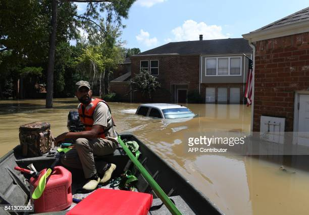 Volunteer rescuer Matt Clarke searches for local residents after a mandatory evacuation was ordered in the area beneath the Barker Reservoir as water...