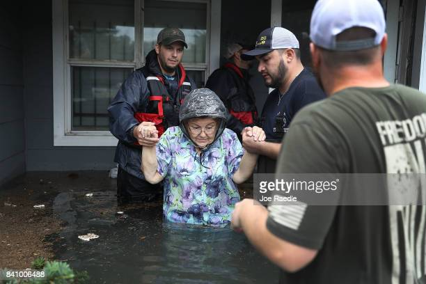 Volunteer rescuer workers help a woman from her home that was inundated with the flooding of Hurricane Harvey on August 30, 2017 in Port Arthur,...