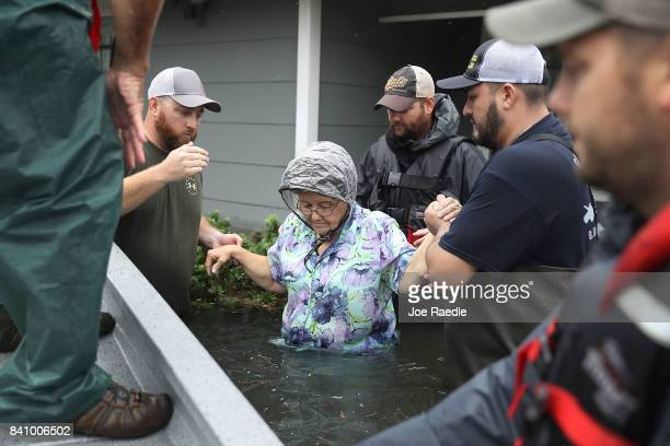 Volunteer rescuer workers help a woman from her home that was inundated with the flooding of Hurricane Harvey on August 30 2017 in Port Arthur Texas...