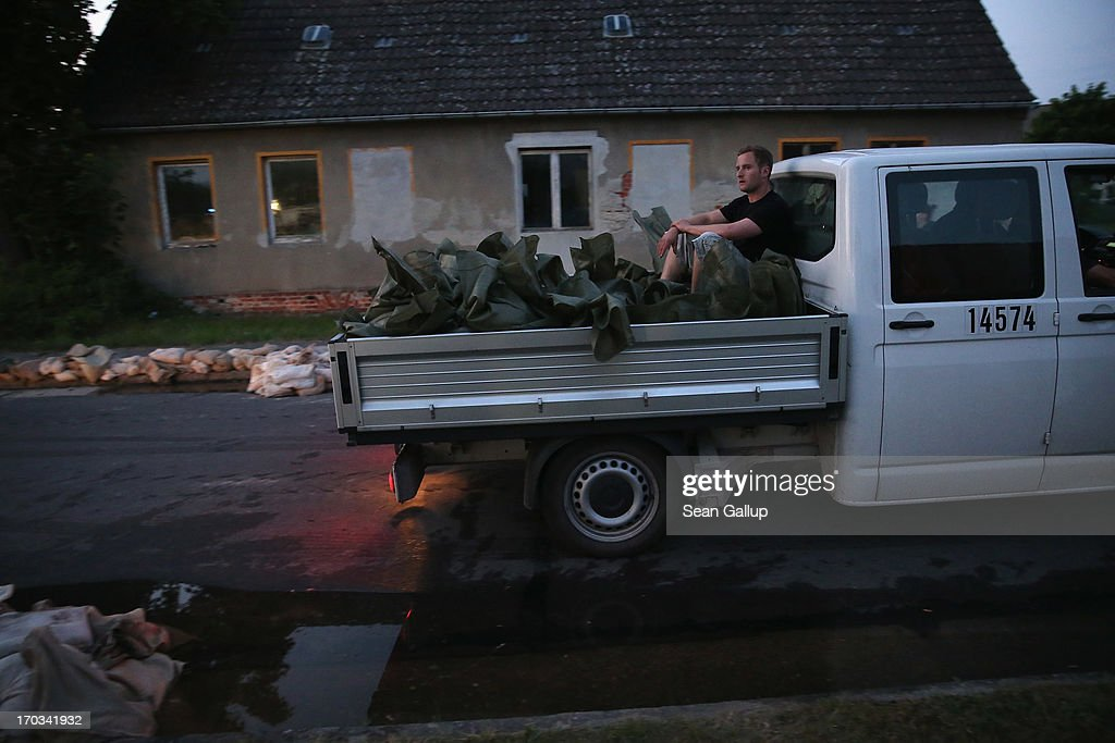 A volunteer rides in the bed of a truck while delivering sandbags to protect local homes from the spreading floodwaters of the Elbe river on June 11, 2013 in Wust, Germany. About a half dozen villages in Stendal county and large tracts of farmland are inundated following the collapse of a dyke at nearby Fischbeck two days ago. Floods have ravaged portions of southern and eastern Germany in the last week, leaving at least seven people dead and forcing tens of thousands to evacuate their homes.