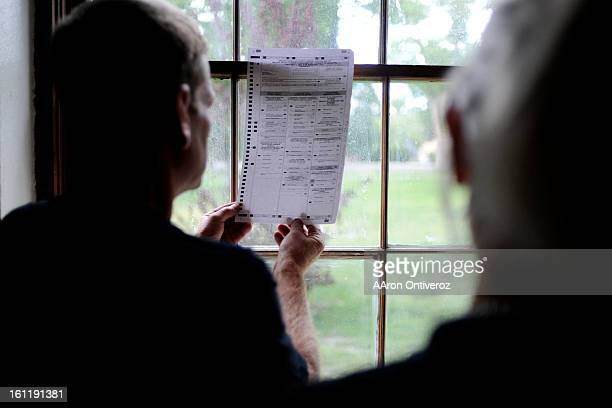 Volunteer Ron Briggs holds a ballot up to the window to decipher markings during a hand review of voted ballots for the clerk and commissioner races...