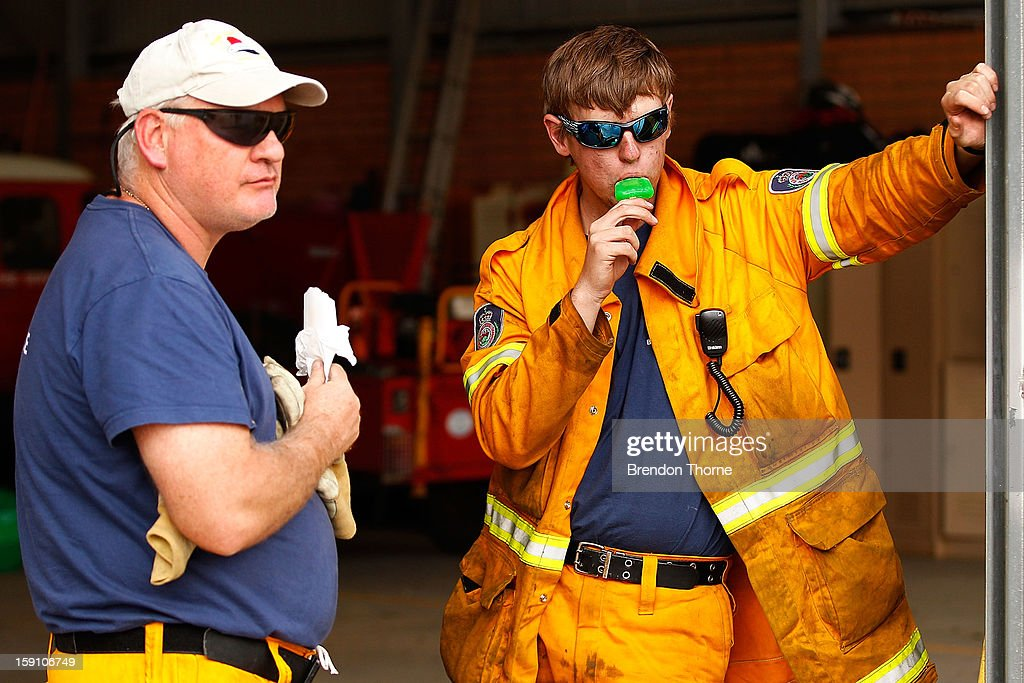 Volunteer Rural Fire Service members from Bungendore RFS cool down by eating ice blocks on January 8, 2013 in Bungendore, Australia. NSW was declared a total fire ban with the Illawarra, Shoalhaven and Southern Ranges regions placed on 'Catastrophic' alert.