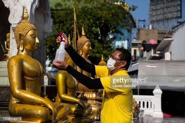 Volunteer sanitizes Buddha statues before witnessing Thai monks taking part in the chant of an ancient prayer designed to ward off the plague at Wat...