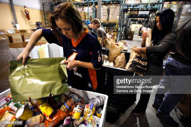 Volunteer Sarah Olson of Louisville empties a bag of canned food while sorting donated food from the 'Let's Bag Hunger' food drive to support the...