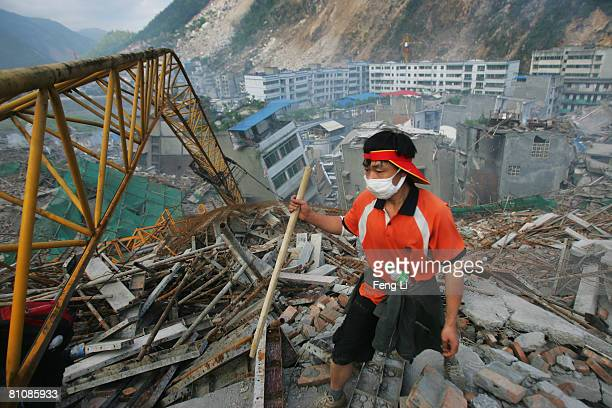 A volunteer searches for victims in the debris of a building on May 14 2008 in Beichuan Town of Mianyang City of Sichuan Province China A major...