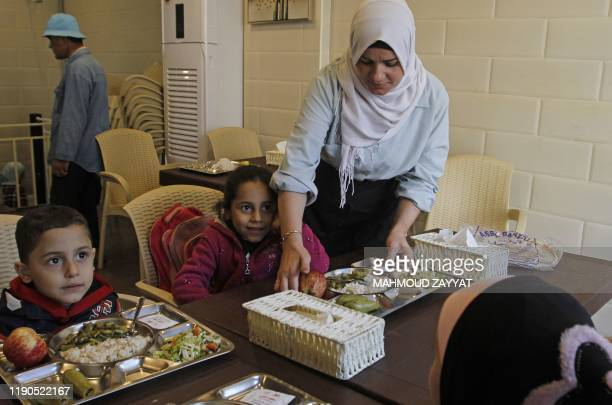 A volunteer serves food to neddy children at a kitchen set up by charity groups in Lebanon's southern city of Sidon on December 7 2019 With volunteer...