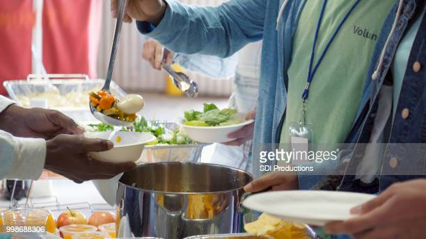 volunteer serves people in homeless shelter - homeless shelter stock pictures, royalty-free photos & images