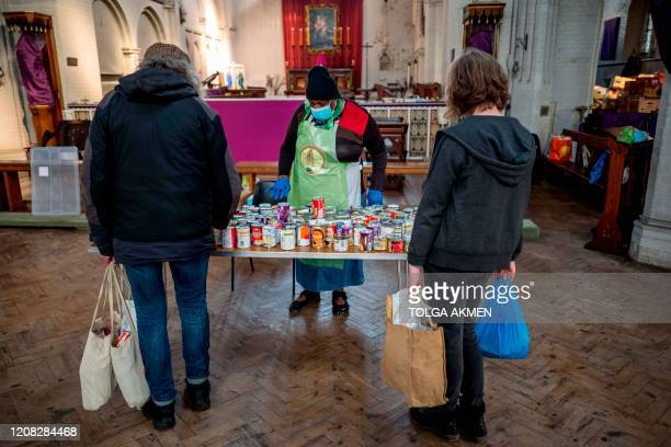 A volunteer serves peopleinneed at a popup shop serving as food bank at St Margaret's Church in Leytonstone amidst the novel coronavirus COVID19...
