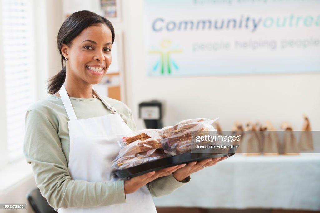 Volunteer serving food in community kitchen : Stock Photo