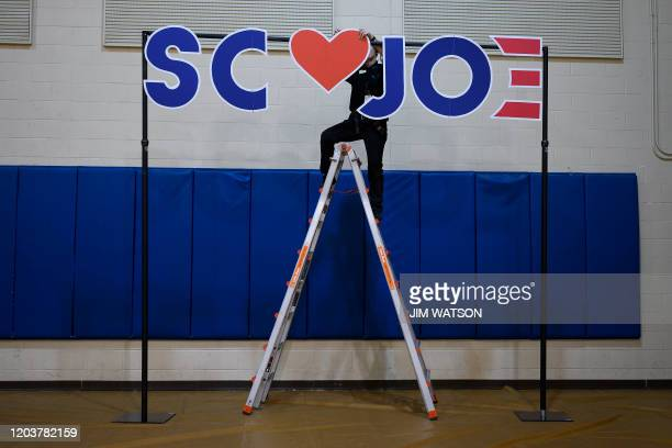 A volunteer sets up a background sign for a Democratic presidential hopeful former Vice President Joe Biden rally in Conway South Carolina on...