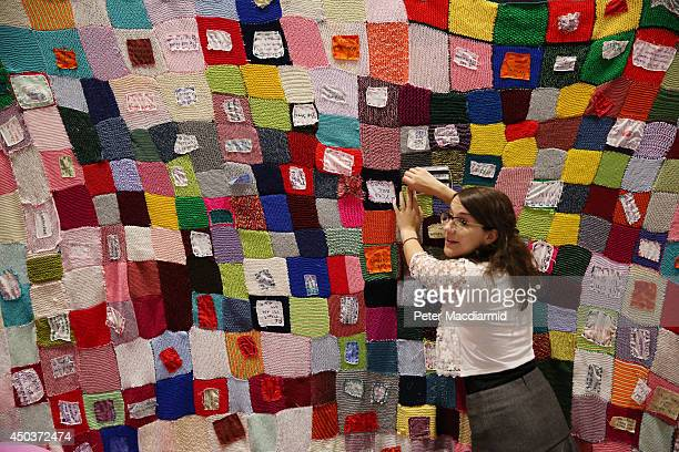 A volunteer sews a message onto a quilt in support of women detained in UK detention centres at the Global Summit To End Sexual Violence In Conflict...