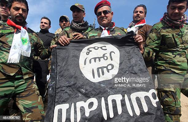 Volunteer Shiite fighters who supports the Iraqi government forces in the combat against the Islamic State group hold a black Islamist flag allegedly...