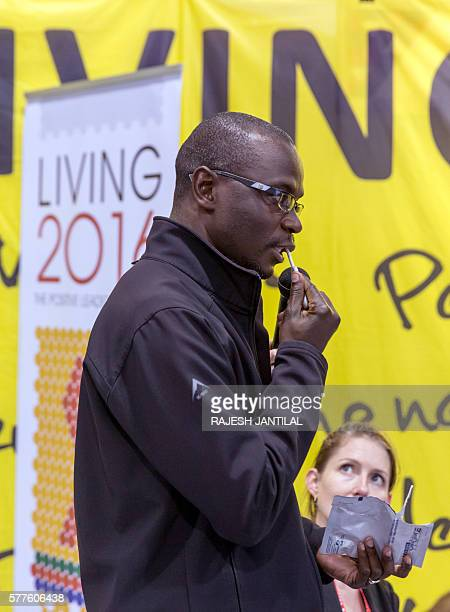 A volunteer shows how to use Ora Quick HIV Self testing device at the Living 2016 Positive Leadership stand during the second day of the 21st...
