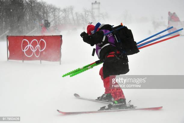 A volunteer skis past a barrier bearing the Olympic rings as the start of the Alpine Skiing Women's Slalom was delayed due to weather conditions at...