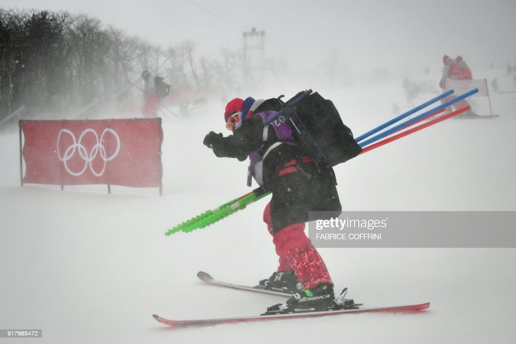TOPSHOT - A volunteer skis past a barrier bearing the Olympic rings as the start of the Alpine Skiing Women's Slalom was posponed due to weather conditions at the Jeongseon Alpine Center during the Pyeongchang 2018 Winter Olympic Games in Pyeongchang on February 14, 2018. / AFP PHOTO / Fabrice COFFRINI