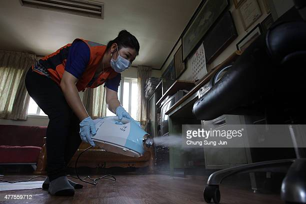 A volunteer spray antiseptic solution in an senior citizen center amid rising public concerns over the spread of MERS virus on June 18 2015 South...