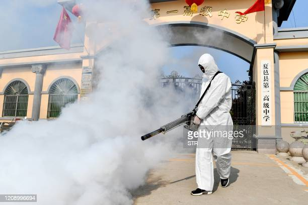 Volunteer sprays disinfectant at a school as the school prepares for students returning after the term opening was delayed due to the COVID-19...