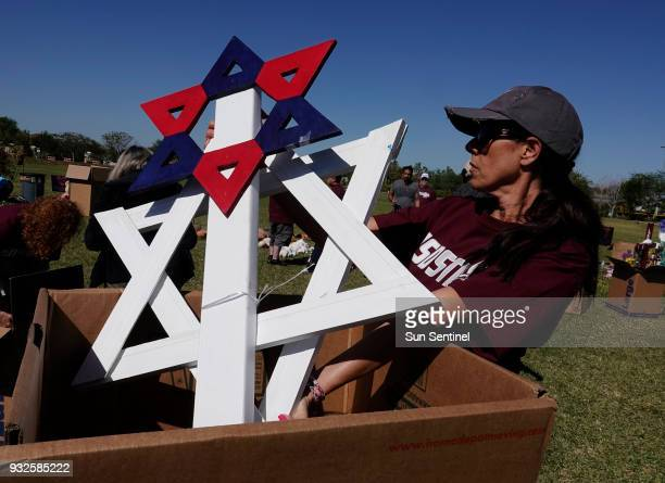 Volunteer Stacey Udine removes items left at the memorials for the Marjory Stoneman Douglas shooting victims Thursday March 15 at Pine Trails Park in...