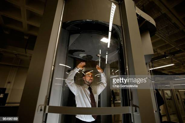 A volunteer stands inside a millimeter wave scanner during a demonstration at the Transportation Security Administration's Systems Integration...