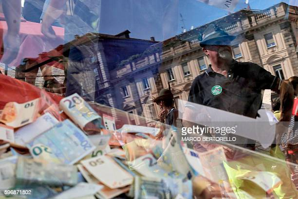 Volunteer stands next to a donation box during a charity event in Piazza San Carlo in Turin, on August 28 whose profits are to help the population...