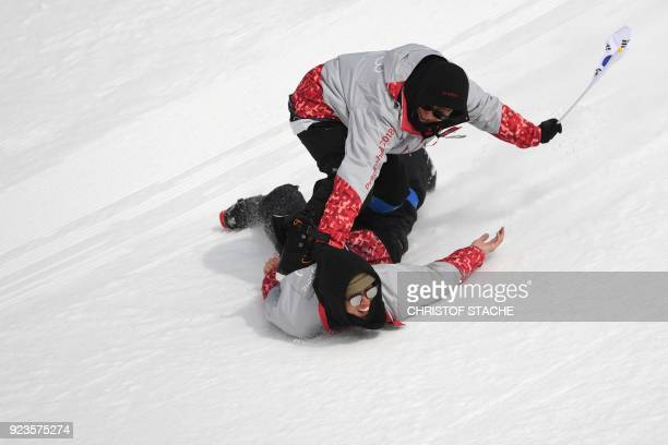 A volunteer stands on another volunteer to slide down the slope after the final of the men's snowboard big air event at the Alpensia Ski Jumping...