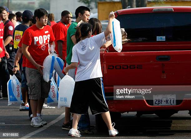 Volunteer students hand out ice and packaged meals at a distribution point at the University of Houston September 19 2008 in Houston Texas Parts of...