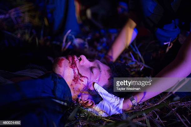 A volunteer supports the neck of a severely injured motorbike accident victim on the side of the road on December 6 2014 in Vientiane Laos Vientiane...