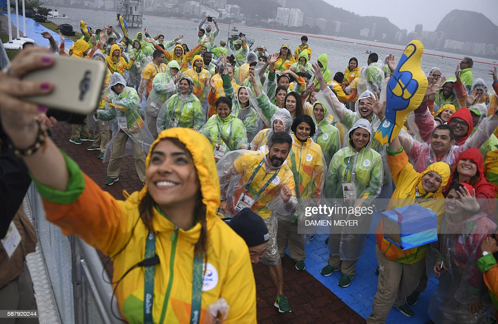 TOPSHOT - A volunteer takes a selfie photo with her mates as they sing and dance at the Lagoa stadium following the cancellation of today's rowing competition, due to bad weather, during the Rio 2016 Olympic Games in Rio de Janeiro on August 10, 2016. / AFP / Damien MEYER