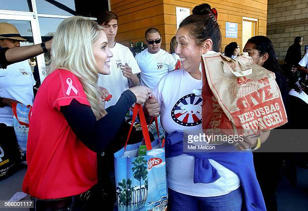 Volunteer Tara McGee, left, hands a bag filled with a frozen turkey to Denise Garcia during the ninth annual Healthy Family Update and Turkey...