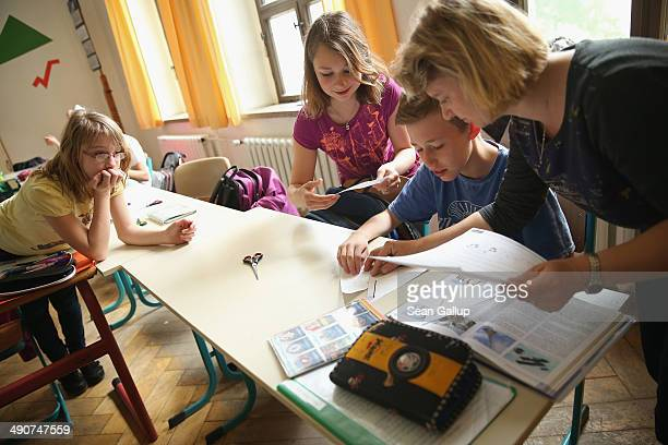 Volunteer teacher Andrea Urban who is also the mother of two of her pupils teaches a technology class as 6th graders Sarah Scheibe Sophie Urban and...