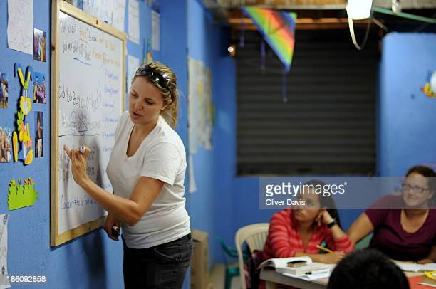 CONTENT] Volunteer teacher Ashley takes English language class as students and other volunteers look on 'Angeles de Medellin' is a program run by...