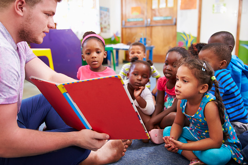 Volunteer teacher reading to a class of preschool kids 484794640