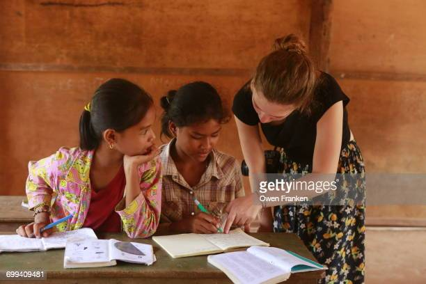 Volunteer teacher with young girls in rural school