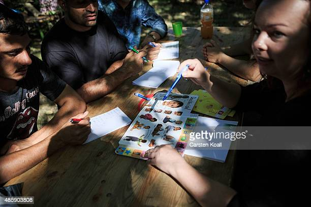 A volunteer teaches refugees in German language in a garden of a private initiative on August 29 2015 in Dresden Germany Germany is expecting to...
